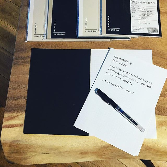 天然木モンキーポッドのワークデスクの上のノートは、2つ折りの紙を束ねたメモパッドのようなノート。 A5の2つ折りを開くとA4サイズに。A4の2つ折りを開くとA3サイズに! 1枚ずつ綺麗に剥がせるだけでなく、特別な製本によりノートがよく開きます。 大成紙器製作所 PAD NOTE GRID*BLACK/WHITE ・A5 500yen+TAX ・A4 700yen+TAX