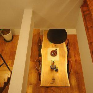 吹き抜けから見下ろす ブラックウォールナット一枚オリジナルmuku-tenのダイニングテーブル。 蝶の形をした黒檀の割れ止め千切りがアクセント。 ハナレアルタナでは、天然木一枚板オーダーテーブルの展示販売をしています。塗装前の一枚板それぞれの表情、カタチ、手触り、サイズを比較、塗装と脚を選択して一点モノのインテリアコーディネートをお愉しみください。