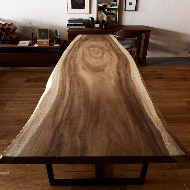 雨降りの日には葉が閉じる事からレインツリーとも呼ばれるモンキーポッドの一枚板テーブル 枝のあった部分を腕を伸ばした手で包み込んでいる様に見える木目ラインがアートな MUKU -TENです。