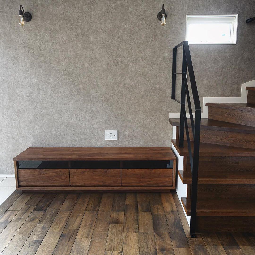 家具納品事例 マスターウォールのtvボード Bass Av Boardは 正面の抽斗に使われている前板が一枚の板で製作されており 木目が端から端まで一繋がりに通っているこだわりの逸品 ウォールナットのフローリングや階段 アイアンの階段手摺りや照明器具 グレーの
